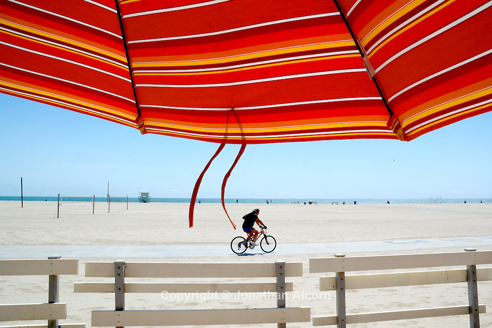 A bicyclist rides on the bike path on a sunny day at the beach in Santa Monica.