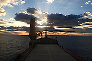 A commercial cargo ship sails into the sunset the ship's bow in the foreground