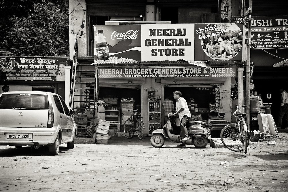 A man starts his scooter in the dirt parking lot of Neeraj General Store. Gurgaon, India. Converted to black and white using Silver Efex Pro.