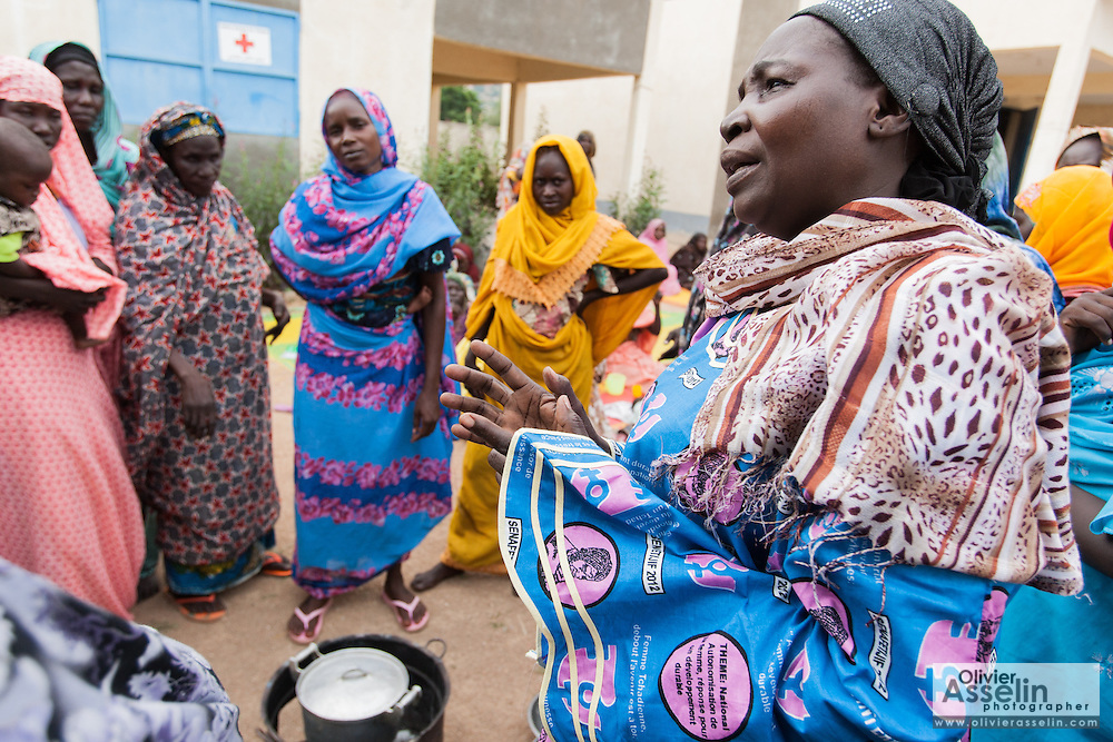 Habsita Moussa, 30, (in blue) stands with other women as they watch while CELIAF president Maimouna Moussa demonstrates how to prepare a nutritional porridge for children from local ingredients during a training session in Mongo, Guera province, Chad on Wednesday October 17, 2012. Local NGO CELIAF is trained by UNICEF to in turn provide women with trainings on nutrition and health issues.