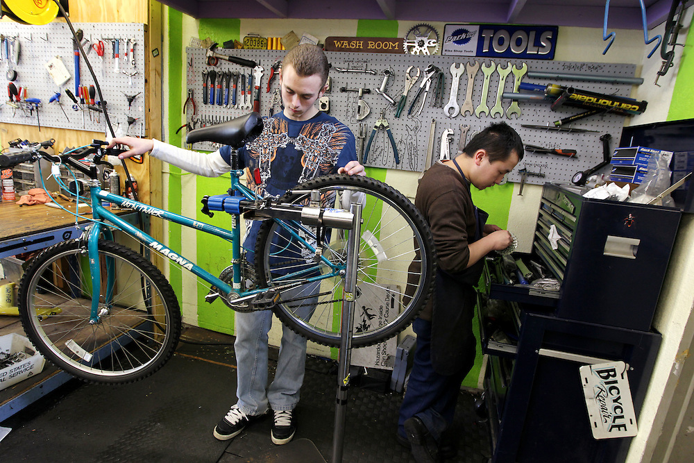 Youth Express apprentice Taylor Altendorfer, 16, left, fixes the brakes on a donated bicycle while assistant manager Yeng Yang gathers some tools at Express Bike Shop in St. Paul, Minnesota.  Yang is also a former apprentice