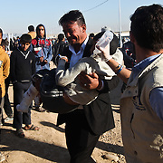 A father walks his wounded son to a medic tent in Mosul at a camp for internally displaced people inKhazir Camp in Northern Iraq.
