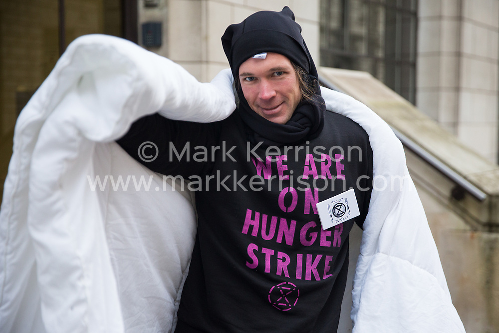 London, UK. 19 November, 2019. Julian, a hunger striking climate activist from Extinction Rebellion, stands outside the Liberal Democrat headquarters on the second day of an 'Election Rebellion' hunger strike with three demands for election candidates: to tell the truth by declaring a Climate and Ecological Emergency, to promote policies to halt biodiversity loss and reduce greenhouse gas emissions to net zero by 2025 and to help the Government create and be led by a Citizen's Assembly on climate and ecological justice.