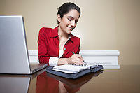 Business woman writing in diary beside laptop in office