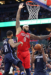 December 22, 2017 - Orlando, FL, USA - The New Orleans Pelicans' DeMarcus Cousins (0) leaps over the Orlando Magic's D.J. Augustin (14) and Bismack Biyombo (11) at the Amway Center in Orlando, Fla., on Friday, Dec. 22, 2017. (Credit Image: © Stephen M. Dowell/TNS via ZUMA Wire)