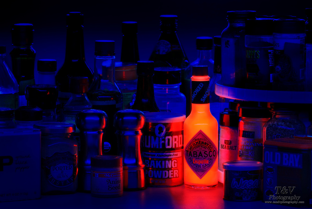 A bottle of Tabasco glows alongside a collecton of spice containers.Black light
