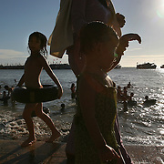 """Children play on the beach in Vung Tau, Vietnam, a popular beach resort a few hours' drive from Ho Chi Minh City. Former glam rock star Gary Glitter is currently behind bars in the resort town, facing charges of child molestation. Glitter, whose real name is Paul Gadd, was convicted in Britain in 1999 of possessing child pornography and served two months in jail. In 2002 he was kicked out of Cambodia, a country with lax regulation of prostitution. Glitter's 1970's hit """"Rock and Roll (Part 2)""""  is played regularly at sporting events throughout North America and Europe."""