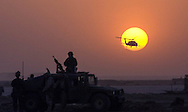 An American Blackhawk helicopter flys off into the setting sun past security forces protecting Air operations at Tallil Air Base, a captured Iraqi air base located in southern Iraq. (Alan Lessig/Air Force Times) (Air Force PA says we can now say the name of this base.)