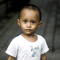 Young asian boy wearing white t-shirt standing in the street