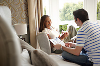 Young adult couple (man and woman) relaxing on bed and chair, by open window, drinking coffee and reading brochure<br /> Bedroom interior<br /> The Escape Hotel<br /> Llandudno<br /> Conwy<br /> North<br /> Bed and Breakfast<br /> Hotels and Accommodation
