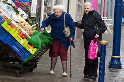© Licensed to London News Pictures. 8/02/2016. Porthcawl, Bridgend, Wales, UK. Two women battle to do the shopping in the centre of town. People struggle to stay on their feet in winds gusting over approximately 60mph. Storm Imogen batters the small Welsh seaside resort of Porthcawl in the county borough of Bridgend on the South coast of Wales, UK. Photo credit: Graham M. Lawrence/LNP