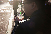 A man walks along a busy backlit street carrying a Starbucks Frappuccino coffee.