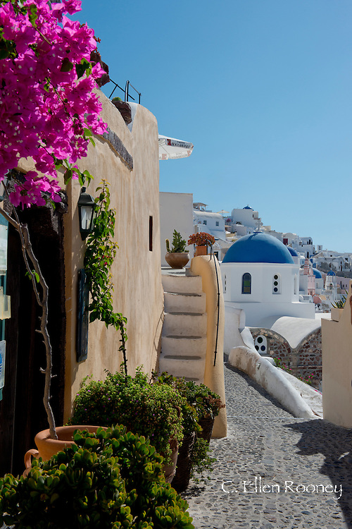 The blue domed<br />  Church of St. Nicholas and bougainvillea around stairs in Oia, Santorini, The Cyclades, The Aegean, The Greek Islands, Greece, Europe