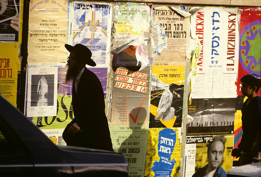 Israel, Jerusalem, Orthodox Jewish man walks past brightly colored posters lining sidewalk in Mea Shearim