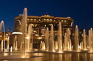 Night view of the Emirates Palace Hotel, Abu Dhabi, with illuminated fountains in foreground.