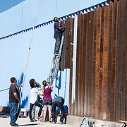 "Artist Ana Teresa Fernández with local Arizonians paint the fence in blue color the theme called ""Erasing the Border"" in Nogales Sonora, Mexico on October 13, 2015. Photo by Nick Oza/ The Arizona Republic"