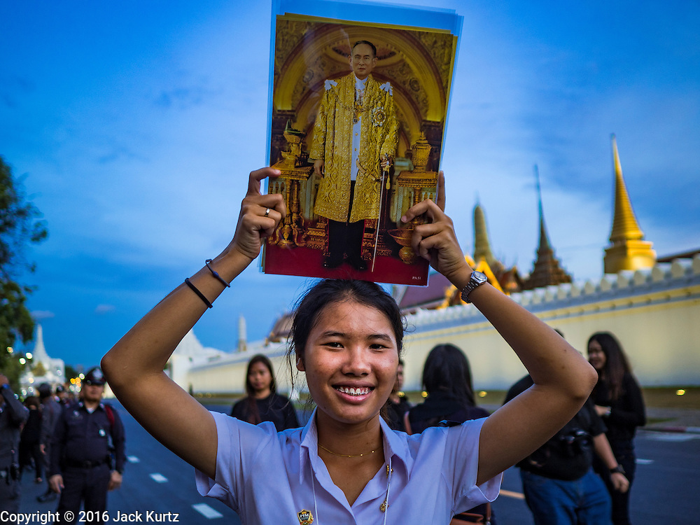 20 OCTOBER 2016 - BANGKOK, THAILAND: A school girl on Sanam Luang holds up a photo of Bhumibol Adulyadej, the King of Thailand, while they mourn the death of the King. Sanam Luang, the Royal Ceremonial Ground, is packed with people mourning the Monarch's death. The King died Oct. 13, 2016. He was 88. His death came after a period of failing health. Bhumibol Adulyadej was born in Cambridge, MA, on 5 December 1927. He was the ninth monarch of Thailand from the Chakri Dynasty and is also known as Rama IX. He became King on June 9, 1946 and served as King of Thailand for 70 years, 126 days. He was, at the time of his death, the world's longest-serving head of state and the longest-reigning monarch in Thai history.        PHOTO BY JACK KURTZ