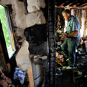 Brad McDouall does through a box of books that were in his house on Catalpa Road in the Wildwood subdivision after it caught fire the evening before.