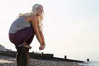 Young woman squatting on wooden pole on beach low angle view portrait