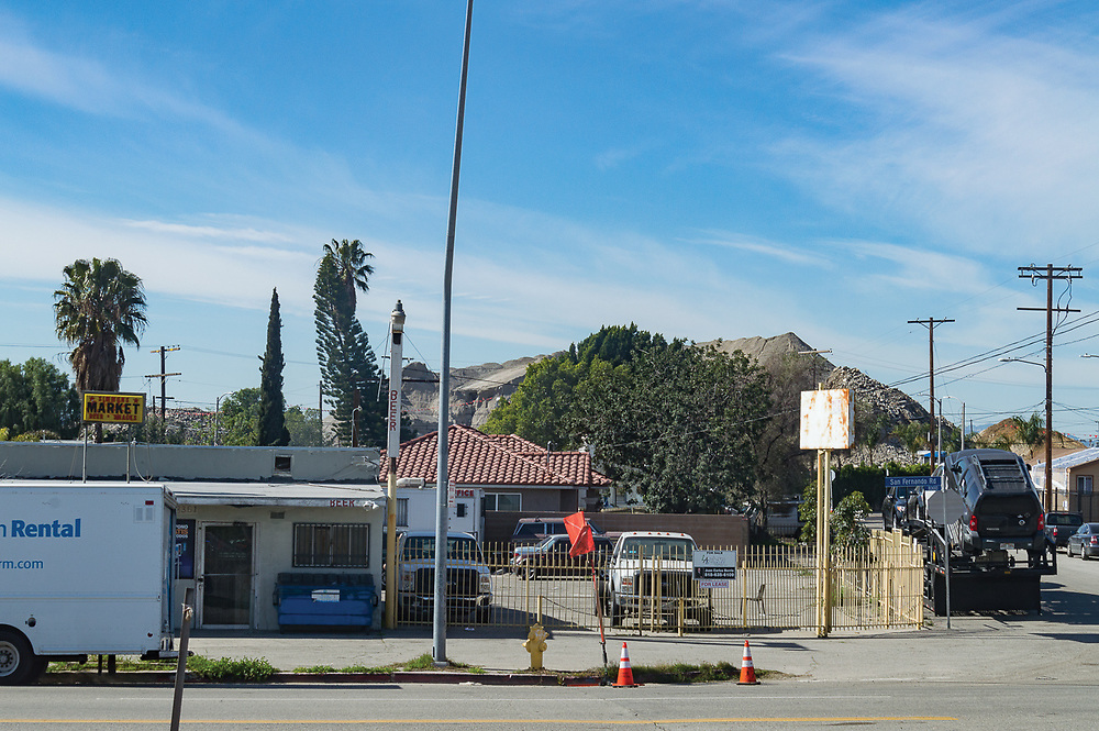 Urban scene of a market with a man made mountain of dirt looming in the background in Sylmar, California