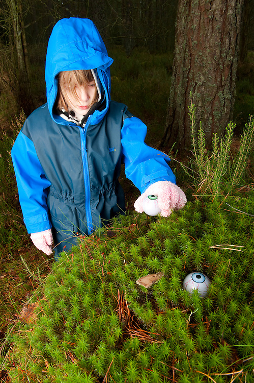 Young girl making a troll's face in Polytrichum moss