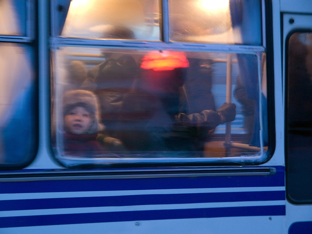 Little boy with a traditional fur cap  behind a window of a Yakutsk bus. Yakutsk is a city in the Russian Far East, located about 4 degrees (450 km) below the Arctic Circle. It is the capital of the Sakha (Yakutia) Republic (formerly the Yakut Autonomous Soviet Socialist Republic), Russia and a major port on the Lena River. Yakutsk is one of the coldest cities on earth, with winter temperatures averaging -40.9 degrees Celsius.