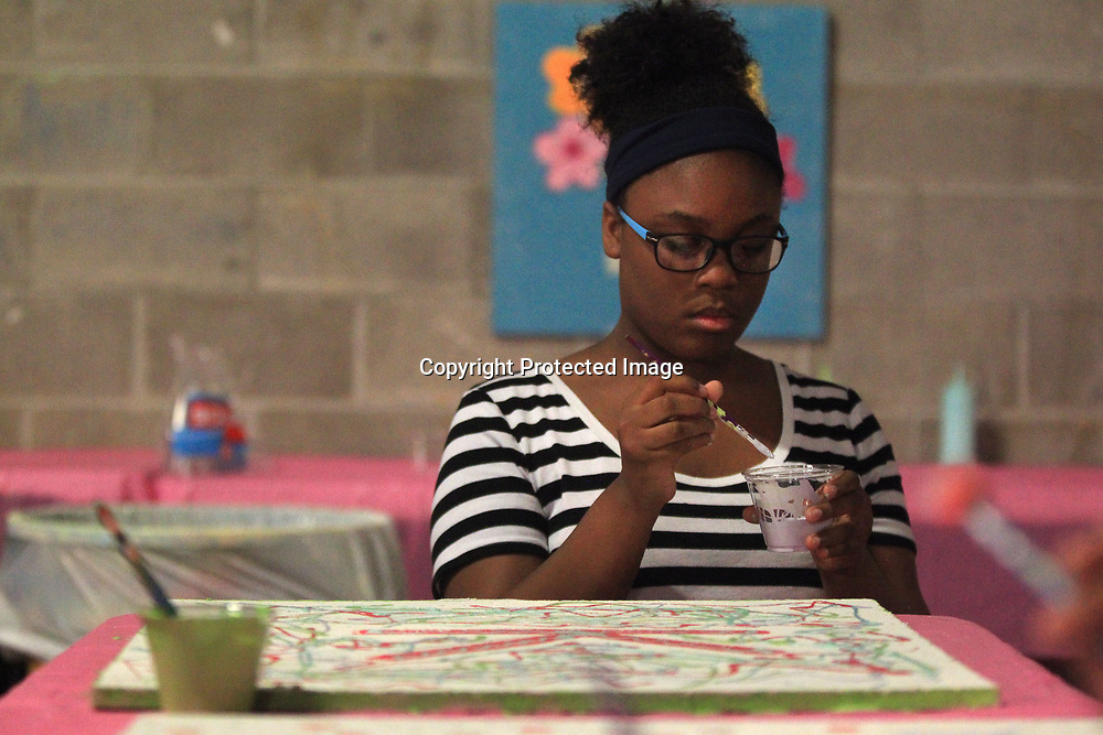 "Kyla Dent, 12, of Tupelo, ""goes with the flow"" as she works on painting her bulletin board project while attending the Junior Auxilary's SHINE camp Tuesday night at HealthWorks in Tupelo. The camp promotes self esteem through acting, art and physical activity."