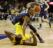 Connecticut's Ryan Boatright, top, tumbles over Marquette's Davante Gardner in overtime of an NCAA college basketball game Tuesday, Jan. 1, 2013, in Milwaukee. Marquette won 82-76 in overtime. (AP Photo/Jeffrey Phelps)