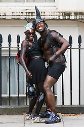 London, August 30th 2015. Smeared in paint, a couple pose for the camera as revellers await the start of the Notting Hill Carnival.