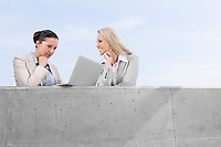 Low angle view of concentrated businesswoman using laptop while standing with happy coworker on terrace against sky