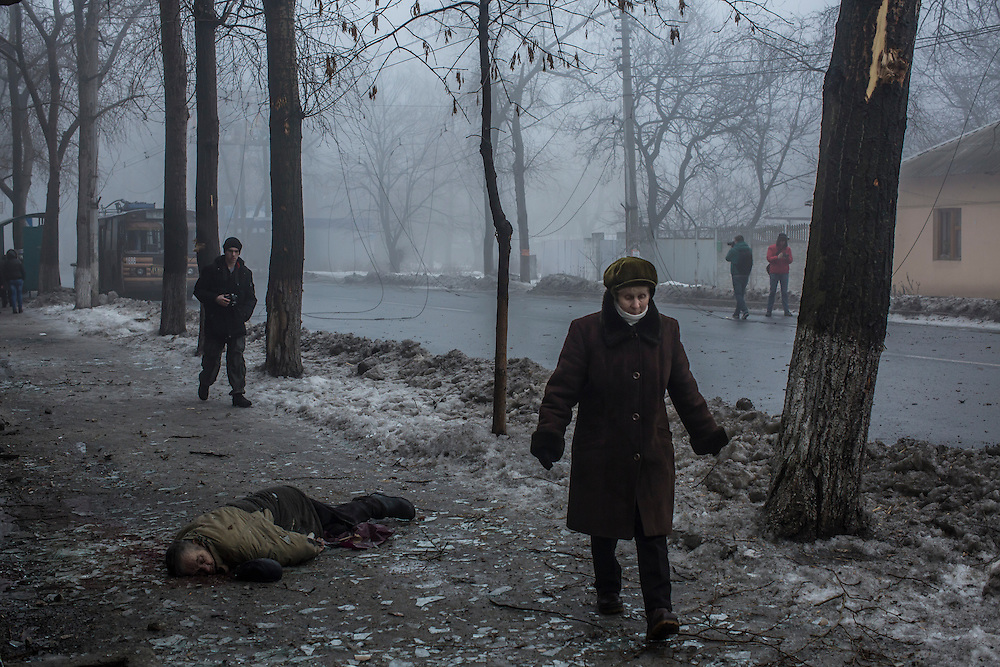 A woman walks past the body of a man killed on the sidewalk when a rocket or mortar struck the road on January 30, 2015 in Donetsk, Ukraine. At least five people were killed in a separate attack nearby when a rocket struck the parking lot outside a center for the distribution of humanitarian aid.