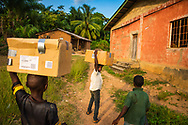 Children carry boxes of medication from the clinic to the village chief's home for nightly safekeeping following the first day of the LCMS Mercy Medical Team on Monday, May 7, 2018, in the Yardu village outside Koidu, Sierra Leone, West Africa. LCMS Communications/Erik M. Lunsford