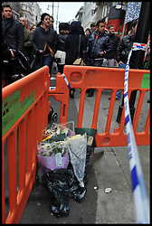 Shoppers walk past flowers left outside a Foot Locker store in Oxford Street after an 18 year old  boy was stabbed to death Oxford Street, central London, on Boxing Day, during the Boxing Day Sales Tuesday December 27, 2011. Photo By Andrew Parsons/i-Images