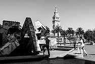 Skateboarders at Vaillancourt Fountain at Justin Herman Plaza at the Embarcadero with San Francisco Ferry Building in background. Black and white.