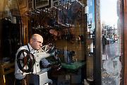 Christos Sollis, of Felix Shoe Repair in Harvard Square, repairs a shoe in his shop, December 4, 2015. (Wicked Local Staff Photo/ Sam Goresh)