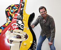 Cuban singer Willy Chirino poses next to a Gibson Guitar at Gibson Showroom in Miami, Florida. (Photo/Cristobal Herrera)