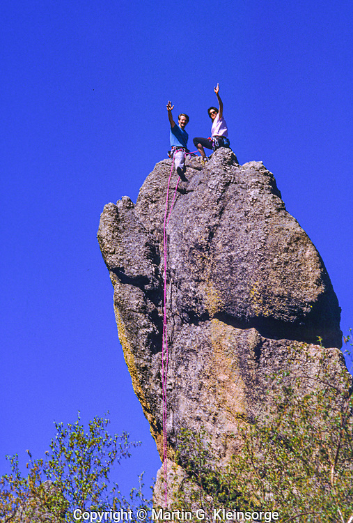 Rock climbers on the tip of a granite spire along the Needles Highway.  Custer State Park, South Dakota.