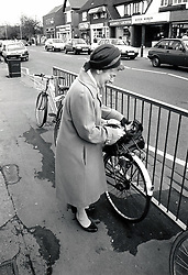 Elderly woman with bicycle, Nottingham, UK 1989
