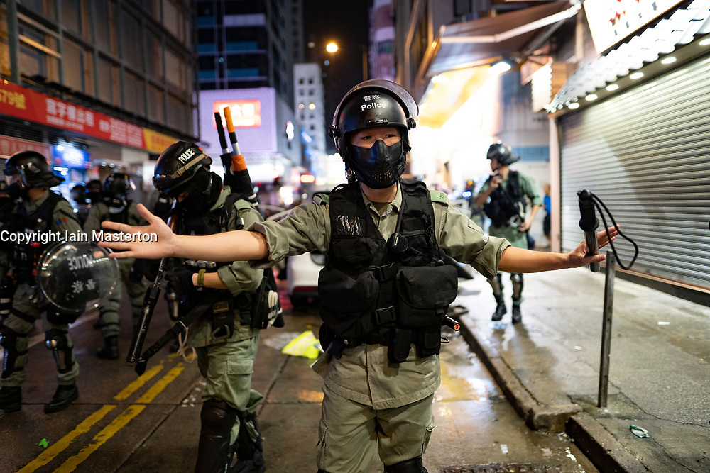 Hong Kong, China. 13th October 2019. Woman suspected of being pro-Beijing is assaulted by pro-democracy protestors in Mongkok district in Kowloon on Sunday evening. This incident was one of several throughout Hong Kong on Sunday which saw acts of vandalism carried out by a minority in the pro-democracy movement. Pic. Police control crowds .  Iain Masterton/Alamy Live News.