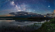 The Milky Way over Maskinonge Lake at Waterton Lakes National Park, Alberta, Canada, on June 17/18, 2018. This was an unusually calm night, allowing the reflections of the stars in the lake waters. Jupiter is in Libra at far right. Saturn is Sagittarius in the Milky Way at left of centre. Scorpius is in between. The sky is deep blue from solstice twilight. <br /> <br /> The Maskinonge area is a sacred site to the Blackfoot Nation. <br /> <br /> This is a two-section panorama, with the ground a stack of 5 exposures for each section to smooth noise, with the sky and stellar reflections coming from one exposure for each segment to minimize trailing. All 25 seconds at f/2.2 with the 20mm Sigma Art lens and Nikon D750 at ISO 3200. Stiching with Photoshop Photomerge.