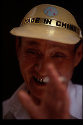 "BEIJING, CHINA - An elderly man sells souvenirs to tourists and sports a hat that reads "" Made In China "". (Photo © Jock Fistick)"