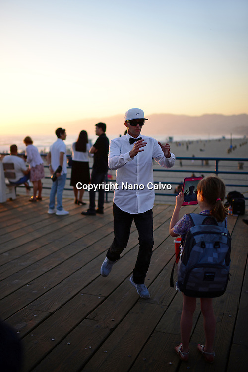 Young girl taking photo of street popping dancer with iPad tablet in Santa Monica pier, California.