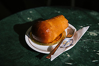 """NAPLES, ITALY - 24 NOVEMBER 2018: A Babà is seen here at Bar Gambrinus, in Naples, Italy, on November 24th 2018.<br /> <br /> My Brilliant Friend (Italian: L'amica geniale) is an Italian-American drama television miniseries based on the novel of the same name by Elena Ferrante. The series follows the lives of two perceptive and intelligent girls, Elena (sometimes called """"Lenù"""") Greco and Raffaella (""""Lila"""") Cerullo, from childhood to adulthood and old age, as they try to create lives for themselves amidst the violent and stultifying culture of their home – a poor neighborhood on the outskirts of Naples, Italy. My Brilliant Friend is a co-production between American premium cable network HBO and Italian networks RAI and TIMvision"""