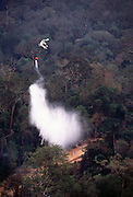 Bell-205 helicopter dropping water bomb on smouldering fire in Borneo.<br />