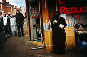 A veiled Muslim woman snacks in front of a shop in the Muslim neighbourhood of Leicester while young men stroll down the street. ..Leicester is expected to be the first city in the UK to have a majority non-white population within the next few years. It is one of the most ethnically-diverse cities in Europe. ....Picture taken April 2005 by Justin Jin