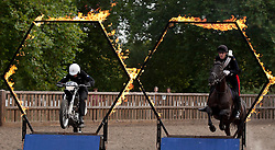 © Licensed to London News Pictures. 12/09/2012. LONDON, UK. Household Cavalry Lance Corporal of Horse Josh Tate, on his horse Evolution, and Royal Signals Corporal Daniel Hale jump through flaming rings in Hyde Park London today (12/09/12) during a taster of some of the acts taking part in the 2012 British Military Tournament. The theme of this year's tournament, involving all arms of the British military, is the life and times of Her Majesty the Queen and takes place at Earls Court in London on the 8th and 9th of December. Photo credit: Matt Cetti-Roberts/LNP