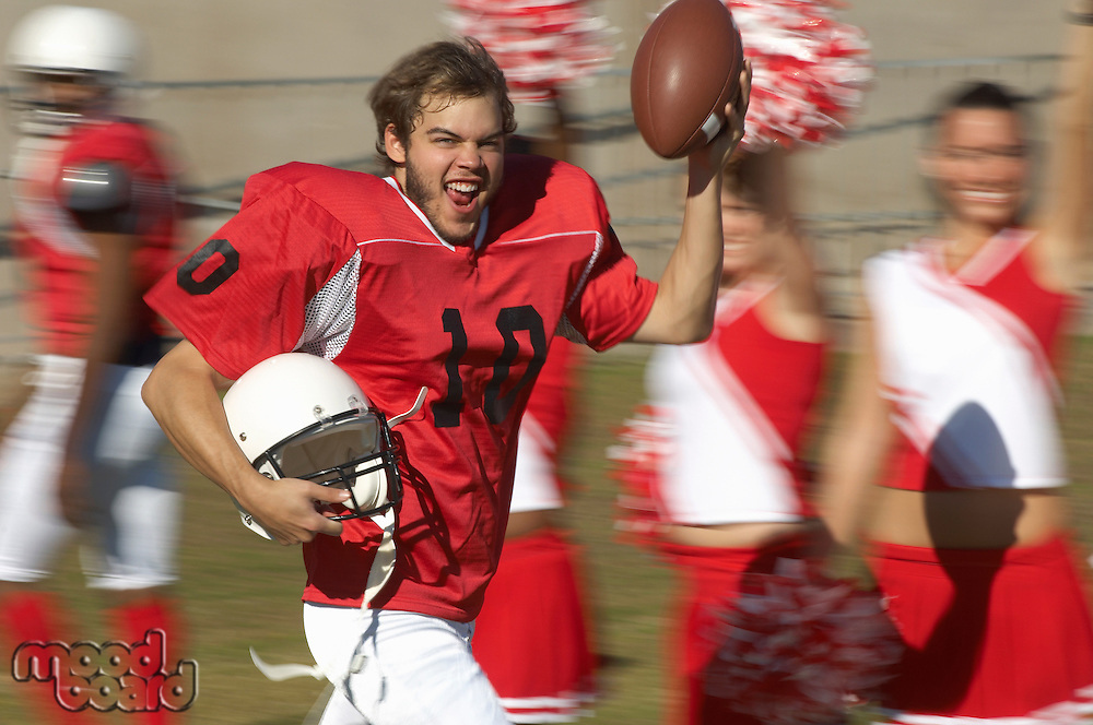 Happy Football Player Running by Cheerleaders