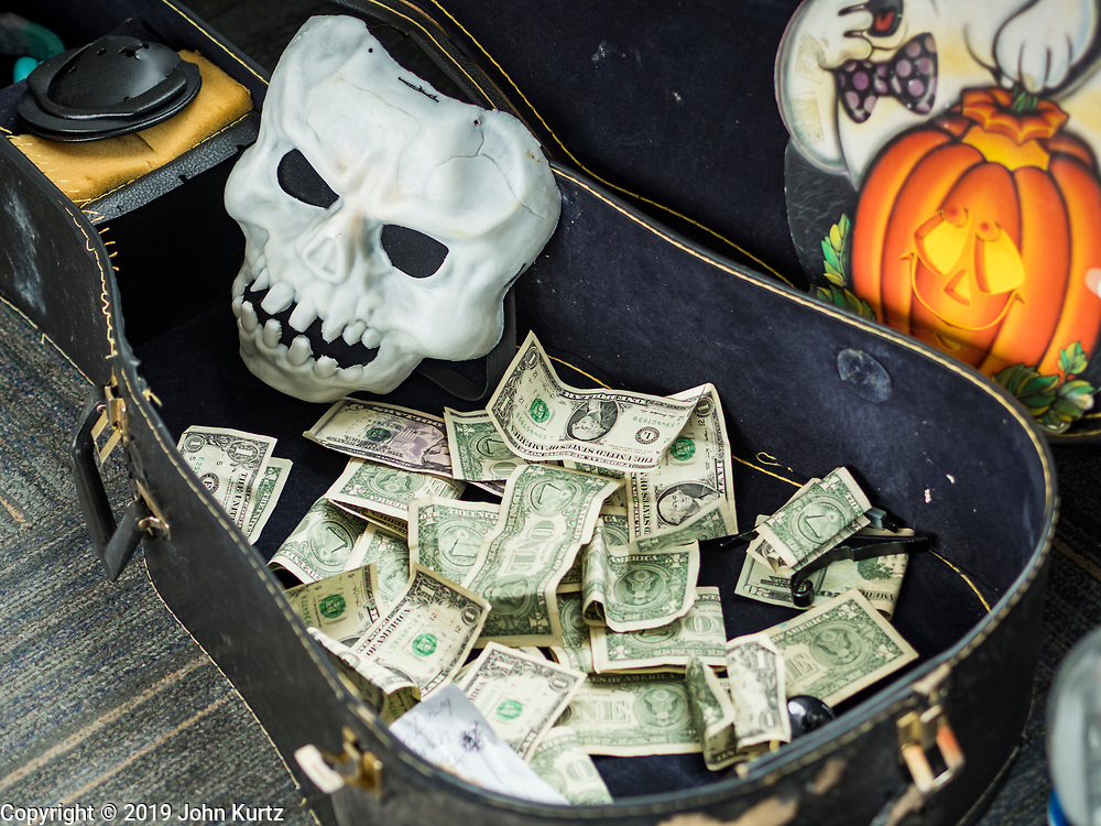 """30 OCTOBER 2019 - DES MOINES, IOWA: The money Randy Kong collected while performing in the Des Moines Skywalk system. Kong said he's been busking for about nine years. He said he started when his band broke up and busking might be way to """"get a hot dog and a coke, and now it's turned into a career."""" He is a regular sight in the skywalk system. In October he hands out candy and sings Halloween themed songs while wearing a """"Phantom of the Opera"""" like mask. In December he does a Christmas themed show and in February he does a Valentines themed show.         PHOTO BY JACK KURTZ"""
