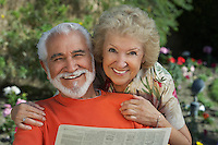 Senior couple reading newspaper in garden, portrait