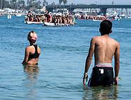 新华社照片,洛杉矶,2017年7月31日<br />     (国际)(4)第二十一届加州长滩龙舟节<br />     7月30日,民众站在水上观赛。<br />     在美国洛杉矶长滩市海滨体育场举行的第二十一届年度长滩龙舟节,吸引百余队上千选手参赛。长滩龙舟节是加州最大的龙舟比赛,同时也展示了中国古代龙舟赛的运动。<br />     新华社发(赵汉荣摄)<br /> Swimmers watch while dragon boat racers prepare to compete during a 500-meter race at the 21st Annual Long Beach Dragon Boat Festival at Marine Stadium in Long Beach, California, the United States, on July 30, 2017. The Long Beach Dragon Boat Festival is held every year in July at Marine Stadium to hosting the largest dragon boat competitions in California. It showcases the ancient Chinese sport of dragon boat racing. (Xinhua/Zhao Hanrong)(Photo by Ringo Chiu)<br /> <br /> Usage Notes: This content is intended for editorial use only. For other uses, additional clearances may be required.
